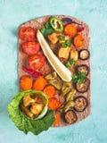 Des morceaux de filet de poulet frit dans une feuille de salade avec les légumes grillés sont présentés sur une tortilla de seigl Image stock