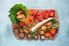 Des morceaux de filet de poulet frit dans une feuille de salade avec les légumes grillés sont présentés sur une tortilla de seigl Photographie stock libre de droits