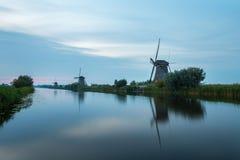 Des moulins à vent sont alignés dans la lumière de soirée au bord de l'eau à la sorte Image libre de droits