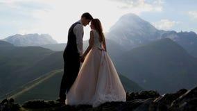 Des nouveaux mariés enamourés sont enchantés avec une soirée merveilleuse d'été dans les rayons du coucher de soleil contre le co banque de vidéos