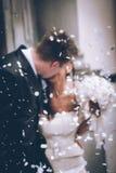 Des nouveaux mariés ils embrassent - foyer defocused intentionnel d'image sur des confettis - les connexions sensorielles image libre de droits