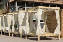 Des pavillons de plage sont alignés dans une rangée sur le sable, le concept des loisirs Photos stock