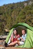 Des personnes de camping - couplez la consommation dans la tente heureuse Photographie stock libre de droits