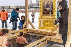 Des personnes russes sont plongées dans un trou de glace le jour de l'épiphanie aux murs de Peter et de Paul Fortress Images libres de droits