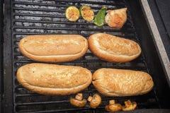Des petits pains de hot-dog sont chauffés sur un gril sur des charbons Nourriture de rue image stock