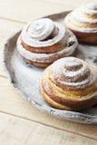 Des petits pains savoureux sont arrosés avec la poudre de sucre sur une lumière fabriquée à la main Images libres de droits