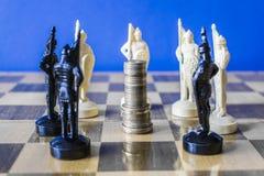 Des pièces de monnaie sont empilées sur un échiquier entouré par les pièces d'échecs noires et blanches Images libres de droits