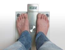 Des pieds du ` s d'homme sur l'échelle de poids - perdez le poids Photos libres de droits