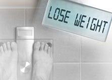 Des pieds du ` s d'homme sur l'échelle de poids - perdez le poids Photo stock