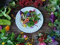 Des plats et les légumes de salade sont placés sur le vieux bois Photo stock