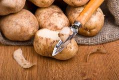 Des pommes de terre fraîches s'enlève avec un couteau de cuisine Photo stock