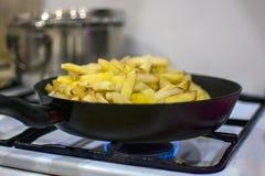 Des pommes de terre sont faites frire sur une cuisinière à gaz photos libres de droits
