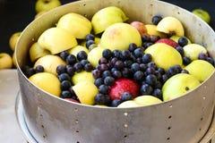 Des pommes et les raisins sont situés dans la cuvette de sokovarki photographie stock