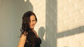Des Porträttanzes der jungen Frau des Brunette rhythmische Gymnastik, modern mit Band im schwarzen sexy Kleid vor den Fenstern stock video