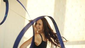Des Porträttanzes der jungen Frauen des Brunette rhythmische Gymnastik, modern mit Band im schwarzen sexy Kleid vor den Fenstern stock video footage
