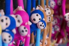 Des poupées de singe sont arrangées dans des couleurs lumineuses Photos libres de droits