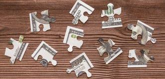 Des puzzles de l'argent de cent-dollar de billets de banque sont démontés dans la perspective d'une texture en bois naturelle Photos libres de droits