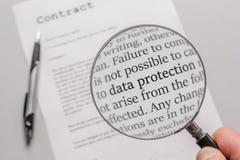 Des règlements de protection des données d'un contrat sont vérifiés soigneusement avec une loupe image libre de droits