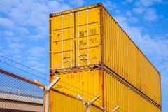 Des récipients de cargaison industriels en métal jaune sont empilés photo stock
