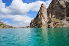 Des roches fines sont reflétées dans le lac haut-montagneux images stock