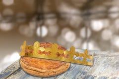 DES rois de Galette, kingcake francês com uma coroa dourada, na tabela de madeira, bolo do esmagamento contra a luz blury fotografia de stock