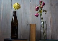 Des roses blanches et rouges dans une bouteille et livres Images libres de droits