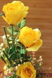 Des roses jaunes sont arrangées dans les bouquets sur un fond brun Photos libres de droits
