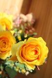 Des roses jaunes sont arrangées dans les bouquets sur un fond brun Photographie stock libre de droits