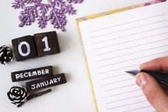 Des salutations de nouvelle année dans un carnet ouvert, elle écrit tenir un stylo Photographie stock libre de droits