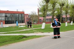 Des sapeurs-pompiers professionnels, les sauveteurs dans les costumes ignifuges protecteurs, les casques et les masques de gaz av image stock