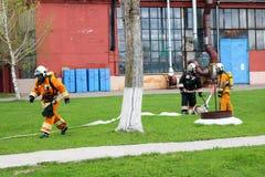Des sapeurs-pompiers professionnels, les sauveteurs dans les costumes ignifuges protecteurs, les casques et les masques de gaz so photographie stock libre de droits
