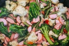 Des saucisses avec le brocoli, le chou-fleur et les haricots verts sont faites frire dans une poêle photographie stock libre de droits