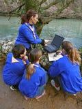 Des scouts sont installés avec l'ordinateur portatif 1 Image stock