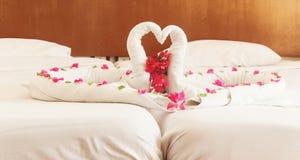 Des serviettes blanches cygnes et coeurs tordus Images stock