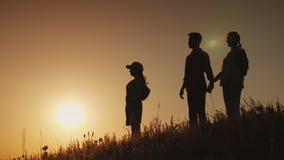 Des silhouettes d'une famille heureuse, ensemble ils rencontrent l'aube dans un endroit pittoresque Image stock