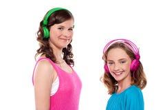 Des soeurs plus âgées et plus jeunes écoutant la musique photographie stock libre de droits