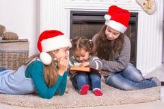 Des soeurs plus âgées lisant une histoire de Noël sa petite soeur Image stock