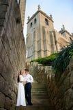 Des Spaßes Umarmung des verheirateten Paars eben nahe der Kirche Lizenzfreies Stockbild