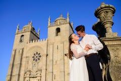 Des Spaßes Umarmung des verheirateten Paars eben nahe der Kirche Stockbilder