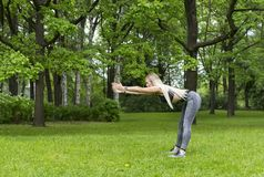 Des sports minces de fille en parc, elle fait les courbures en avant photos libres de droits