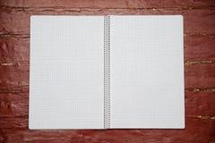 Des Spotts offenes Notizbuch oben in einem Käfig auf einem Frühling, weiße Blätter formatieren Lizenzfreie Stockbilder