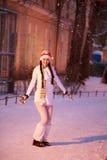 Des Sylvesterabends Das Mädchen in einem weißen Kleid, das unter dem Schneien steht Lizenzfreie Stockbilder
