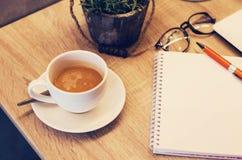 Des tasses de café sont placées sur la table avec des carnets avec des fleurs Photo stock