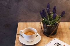 Des tasses de café sont placées sur la table avec des carnets avec des fleurs Photos libres de droits