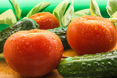 Des tomates rouges mûres, concombres verts, des plumes d'oignon vert sont couvertes de grandes gouttes de l'eau Photos stock