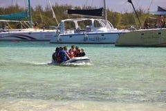 Des touristes sont transportés en le petit bateau d'un catamaran sur l'île de Gabrielle le 24 avril 2012 en Îles Maurice Photographie stock libre de droits