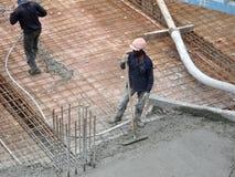 Des travailleurs de la construction nivelant le béton humide a été versés photos libres de droits