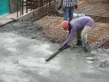 Des travailleurs de la construction nivelant le béton humide a été versés images libres de droits