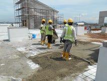 Des travailleurs de la construction nivelant le béton humide a été versés photographie stock