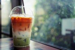 Des trois couches glacées de boisson se composent du thé thaïlandais, du lait et du thé vert dans la tasse en plastique avec le f images libres de droits
